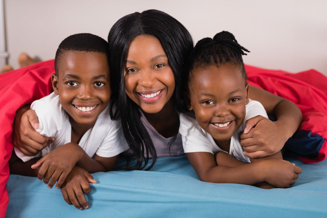 Portrait of smiling woman with children lying on bed at home Free Stock Images from PikWizard