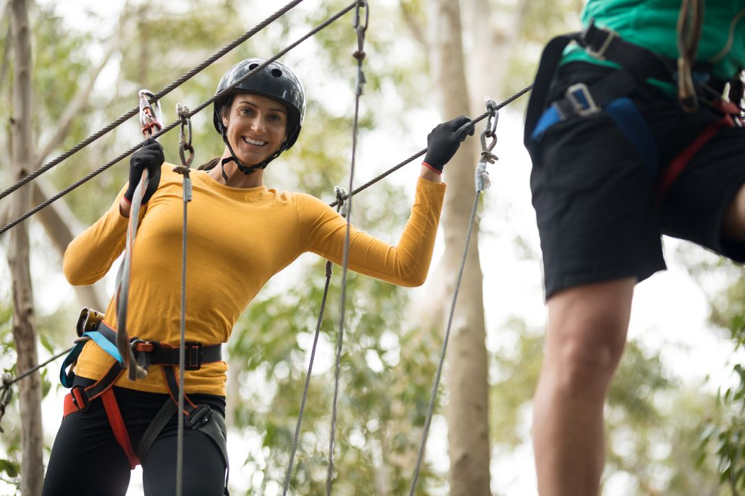 Smiling woman enjoying zip line adventure in park Free Stock Images from PikWizard
