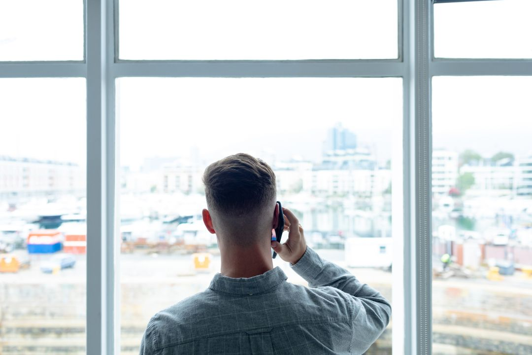 Rear view of Caucasian businessman talking on mobile phone near window in a modern office
