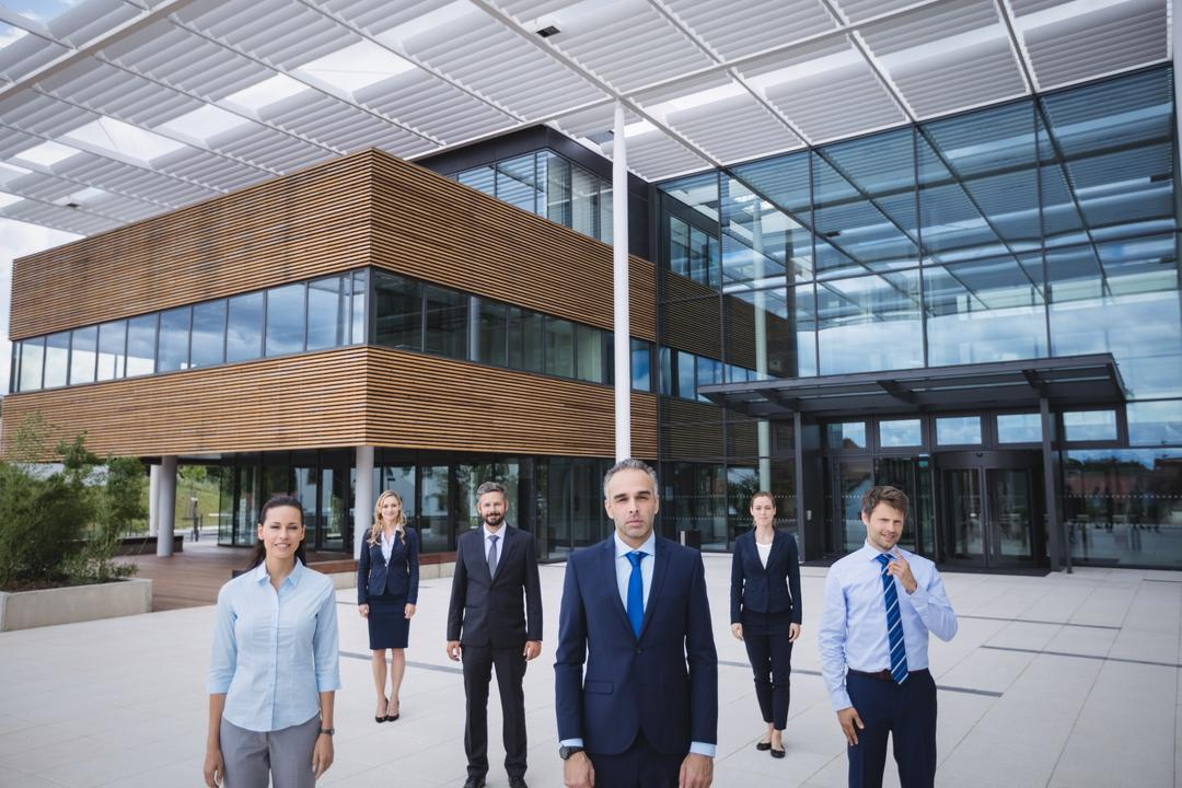 Group of confident businesspeople standing outside office building