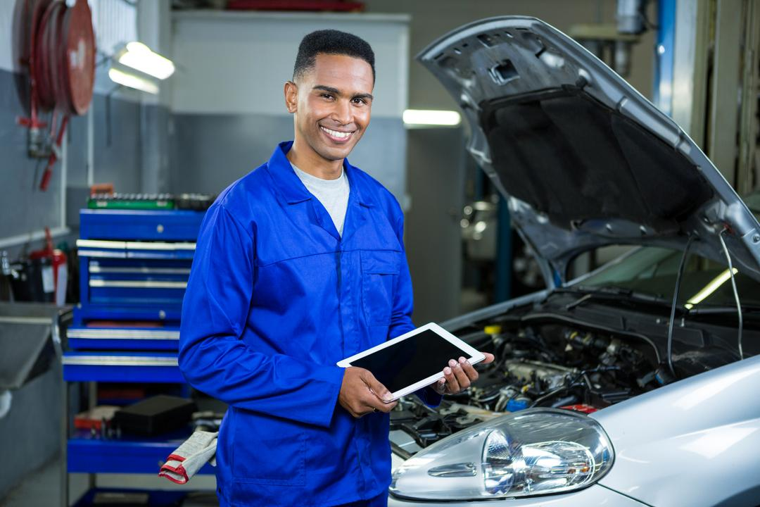 Portrait of happy mechanic using digital tablet at repair garage Free Stock Images from PikWizard