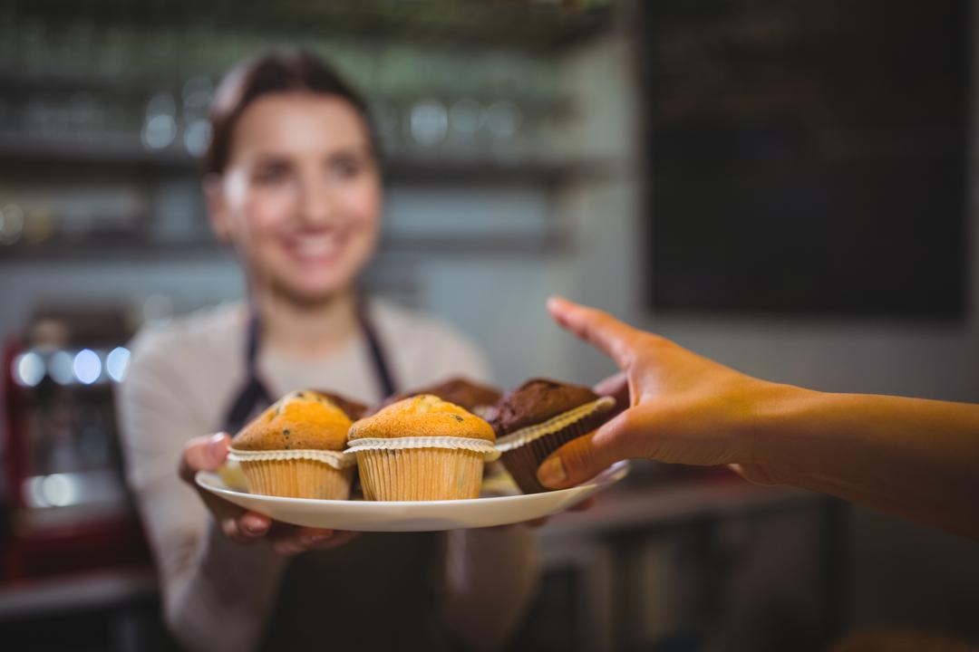 Waitress serving a plate of cupcake to customer in café Free Stock Images from PikWizard