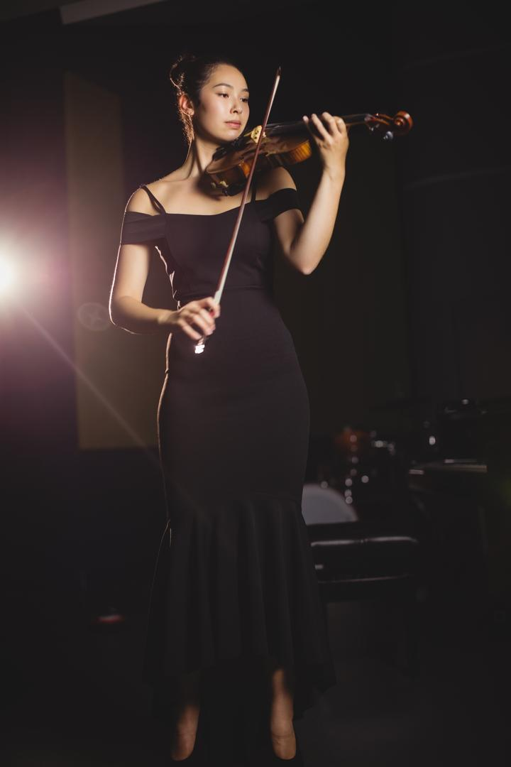 Female student playing violin in a studio