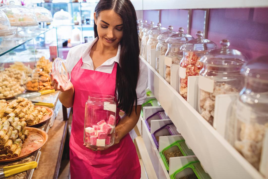 Female shopkeeper holding jar of turkish sweets at counter in shop Free Stock Images from PikWizard