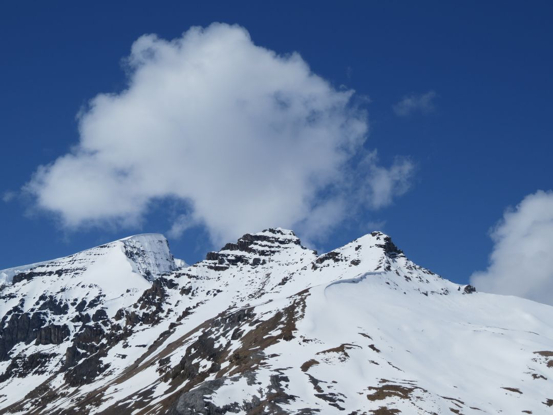 Rock Mountain Covered With Snow Under Blue Sky