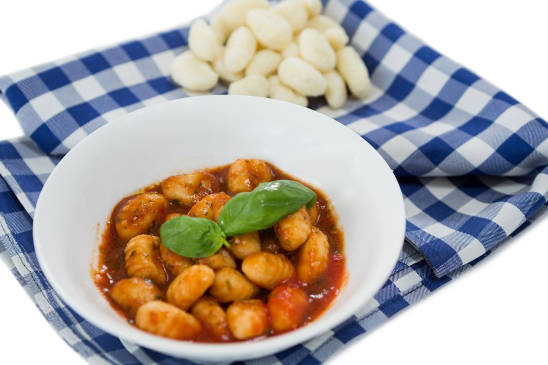 Close up of gnocchi pasta in bowl on napkin against white background Free Stock Images from PikWizard