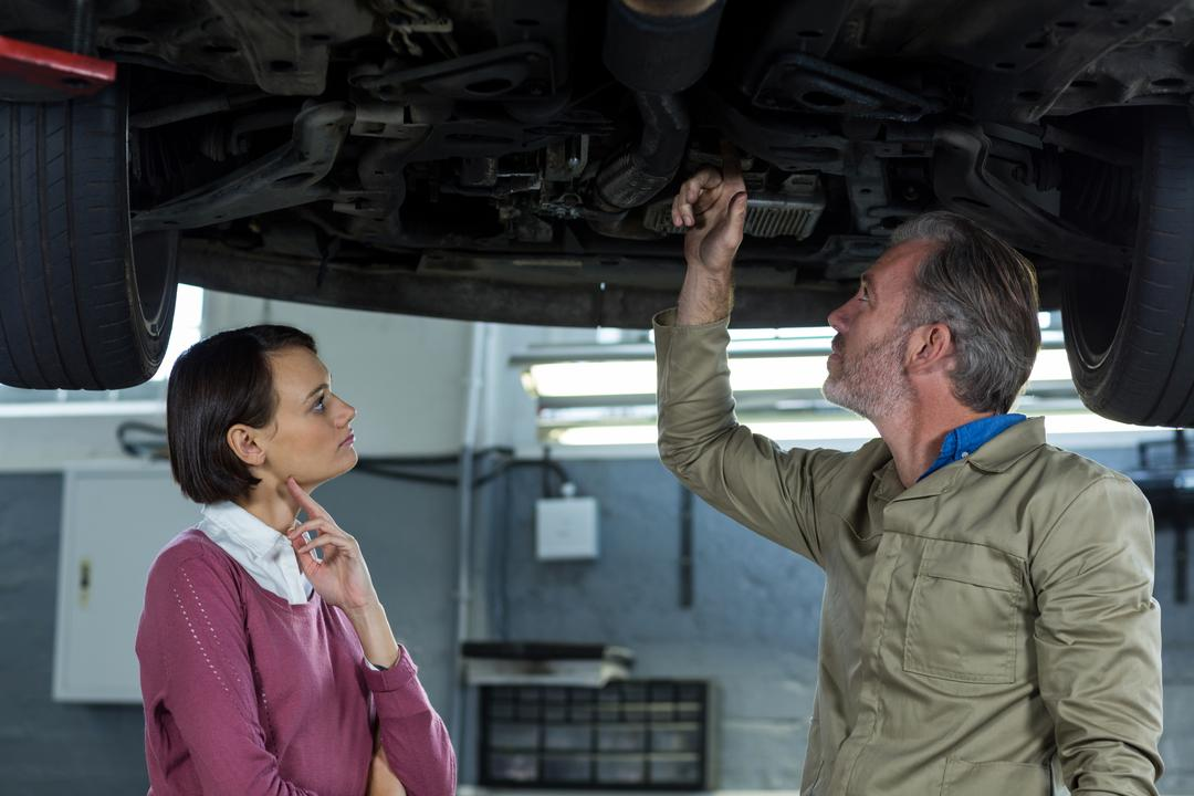 Mechanic showing customer the problem with car at the repair shop