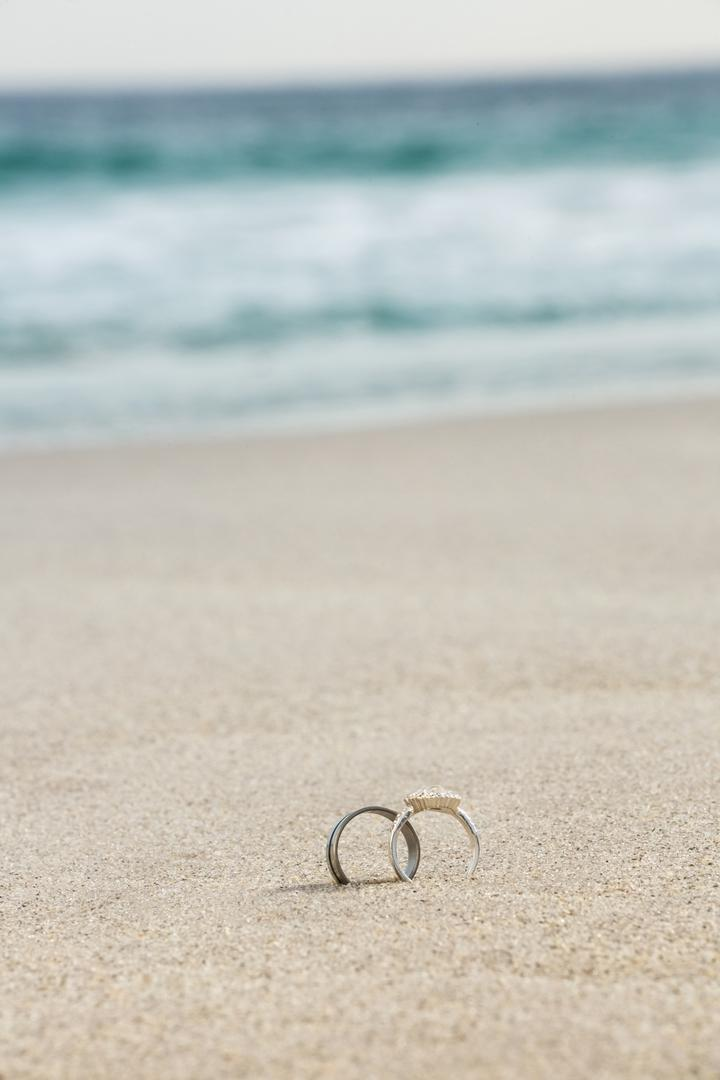 Wedding rings on sand at beach