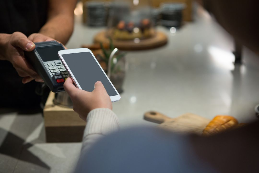 Woman using phone to pay for bill