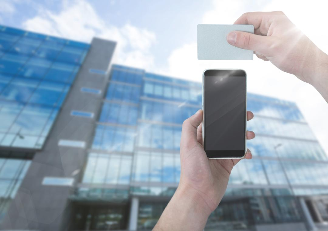 Digital composite of Hand with phone and card against blurry building with flare