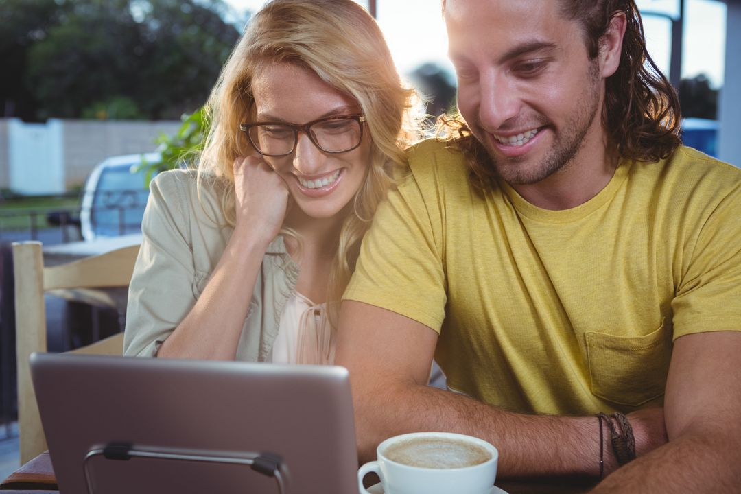 Happy young couple using digital tablet while having coffee in cafeteria Free Stock Images from PikWizard