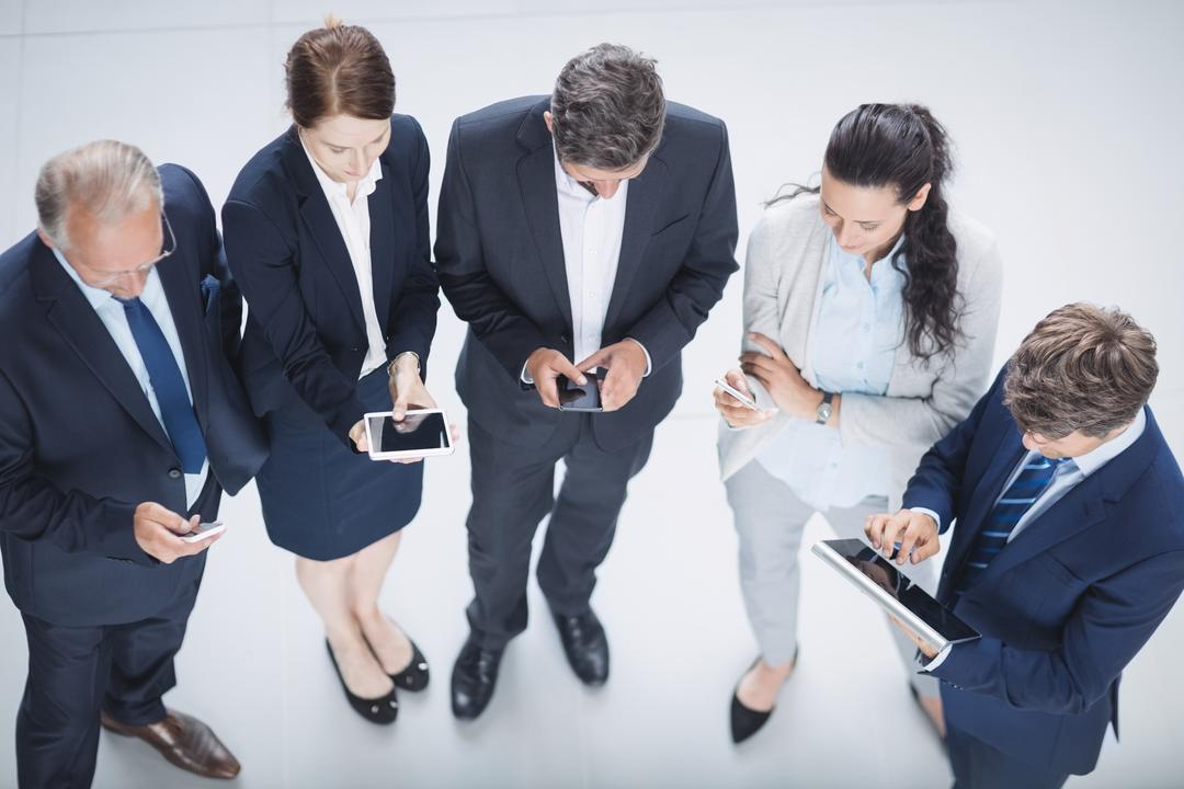 Businesspeople using mobile phone and digital tablet