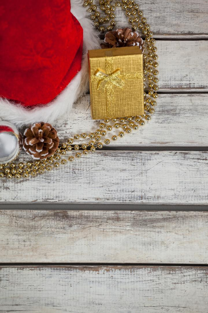 Close-up of Christmas decoration, gift and santa hat kept on wooden table during Christmas time