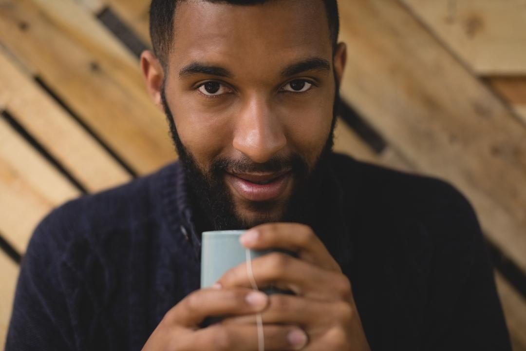 Close up portrait of young man having coffee while sitting in cafe