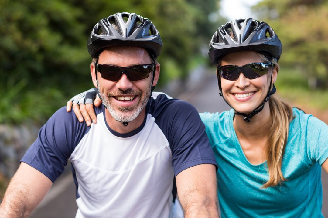 Smiling athletic couple wearing helmets while riding bicycle Free Stock Images from PikWizard