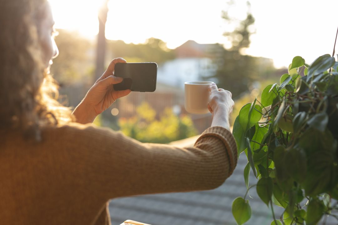 Woman taking a video of her coffee with mobile phone