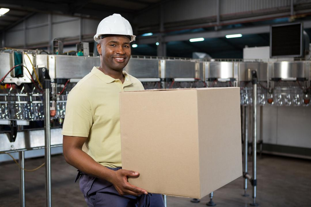 Portrait of smiling male employee carrying cardboard box in juice factory