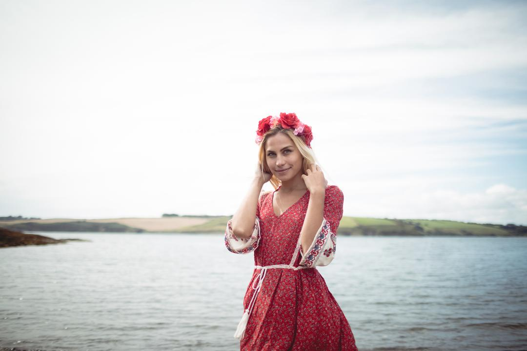 Carefree blonde woman wearing a flower tiara standing near a river