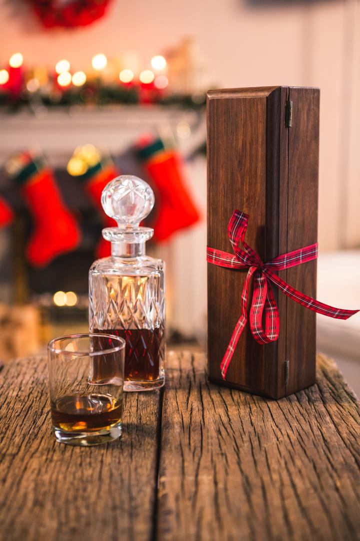 Close-up of bottle of whiskey, glass and gift box on wooden table