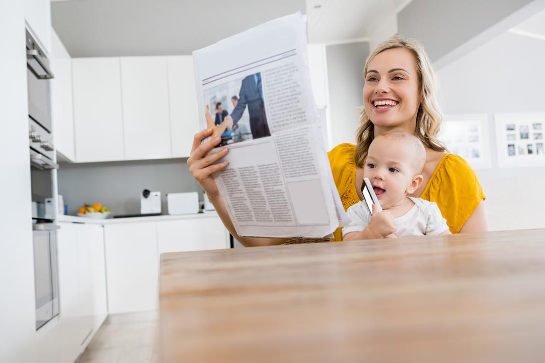 Mother reading newspaper with baby boy in kitchen at home Free Stock Images from PikWizard