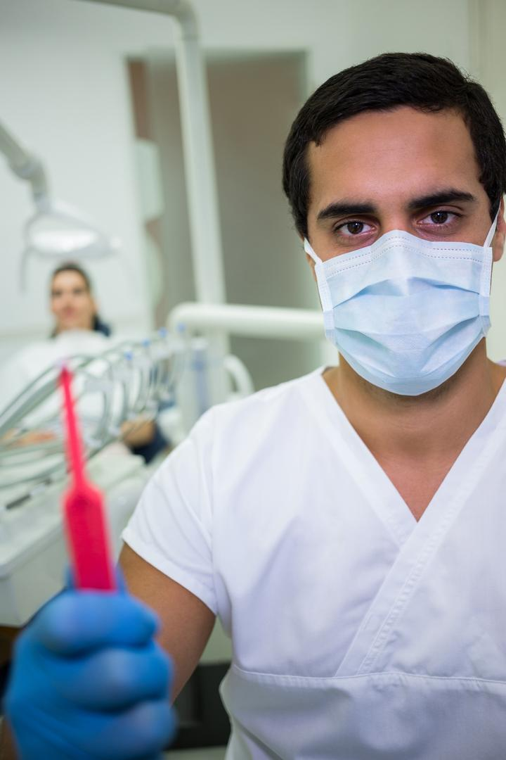 Portrait of dentist holding dental tools in dental clinic