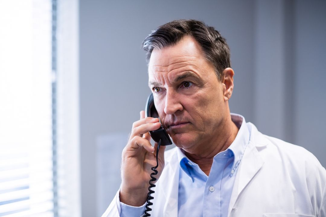Male doctor interacting on phone in clinic Free Stock Images from PikWizard