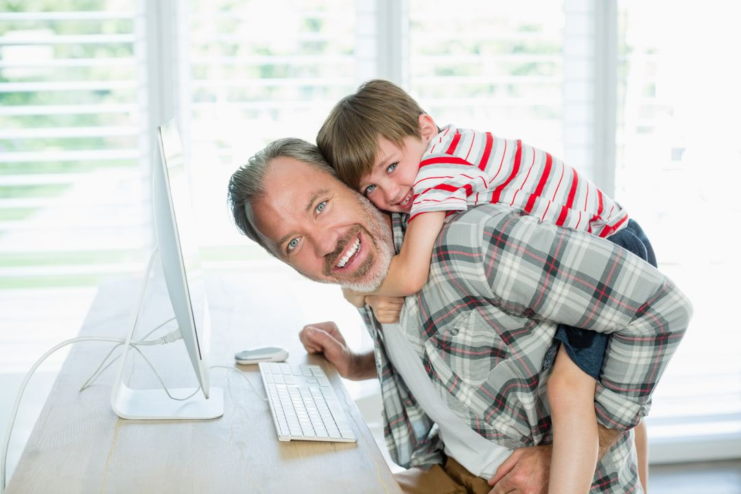 Portrait of playful father and son working on computer at home