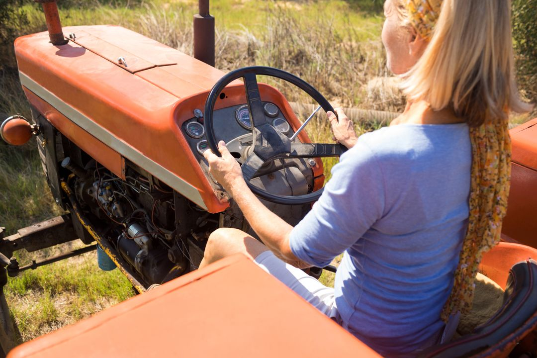 Rear view of woman driving tractor in olive farm on a sunny day Free Stock Images from PikWizard
