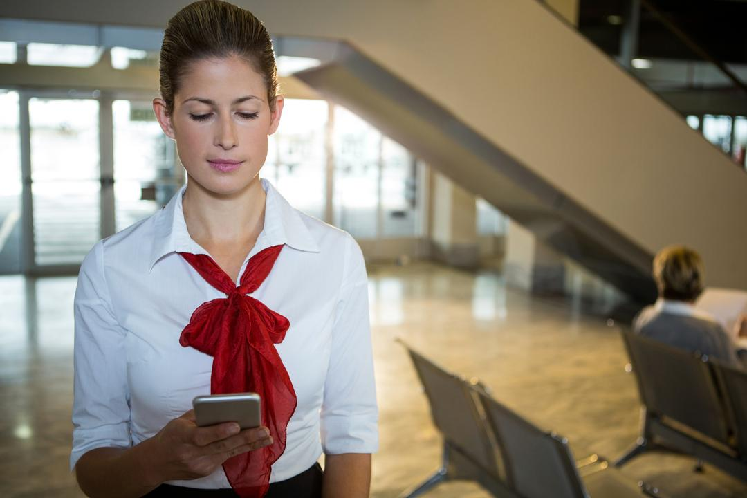 Air hostess using her mobile phone at airport terminal