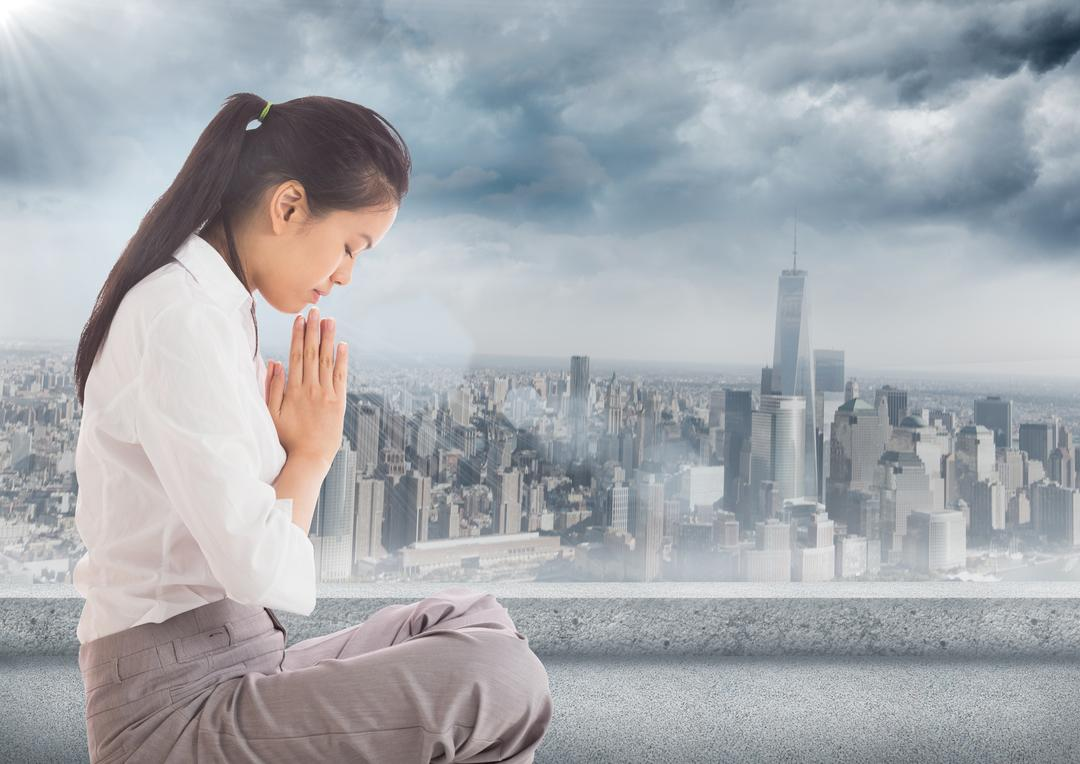 Digital composite of Business woman with flare praying against grey skyline and clouds
