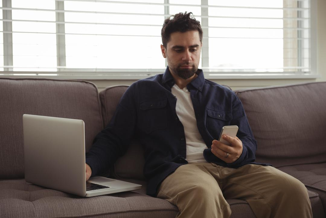 Man using mobile phone and laptop on sofa at home Free Stock Images from PikWizard