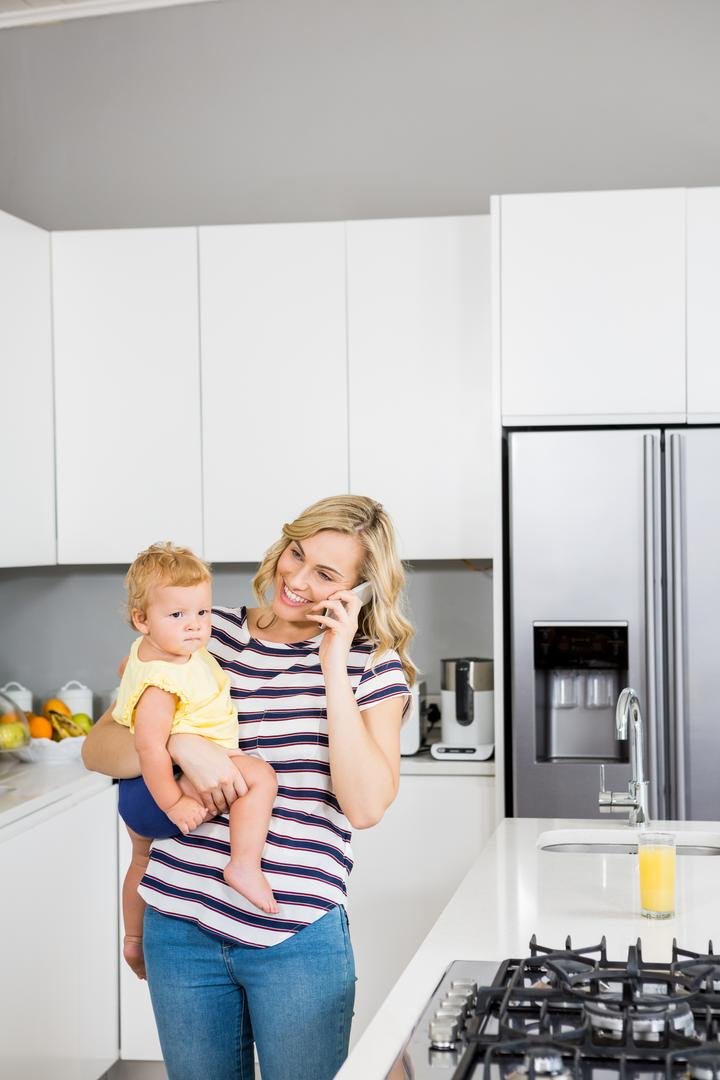 Mother talking on mobile phone while holding her baby girl in kitchen at home
