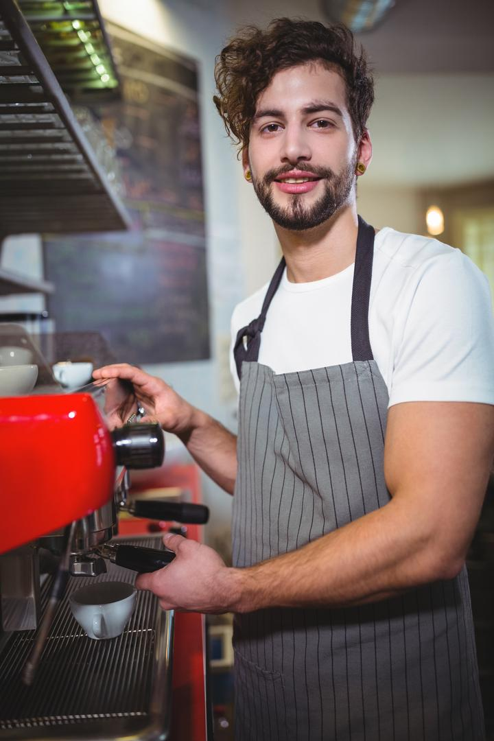 Portrait of waiter making cup of coffee at counter in kitchen at café