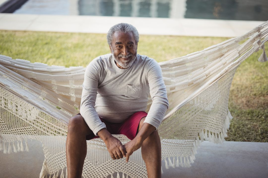 Portrait of smiling senior man sitting on hammock Free Stock Images from PikWizard