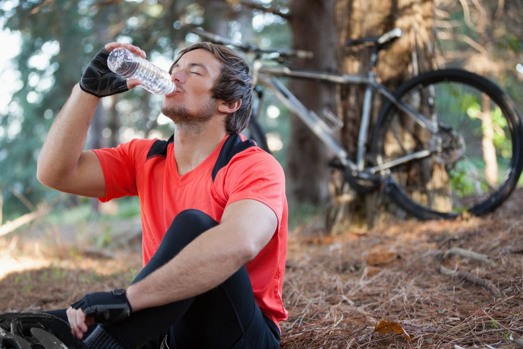 Male mountain biker drinking water in the forest Free Stock Images from PikWizard