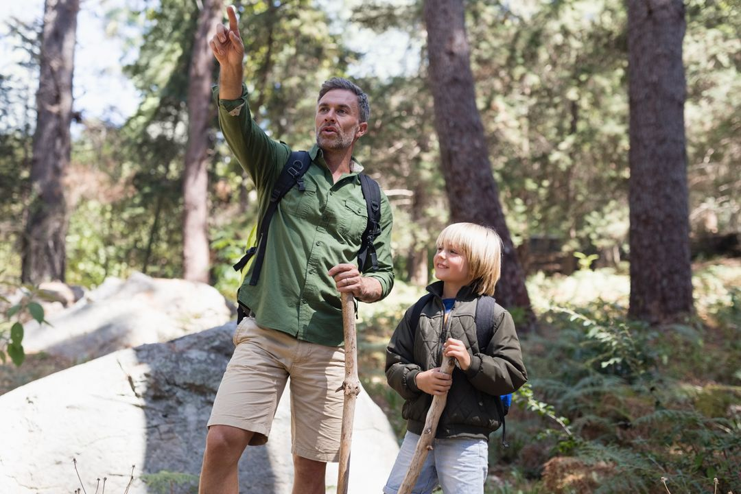 Father pointing away while standing with son in forest Free Stock Images from PikWizard