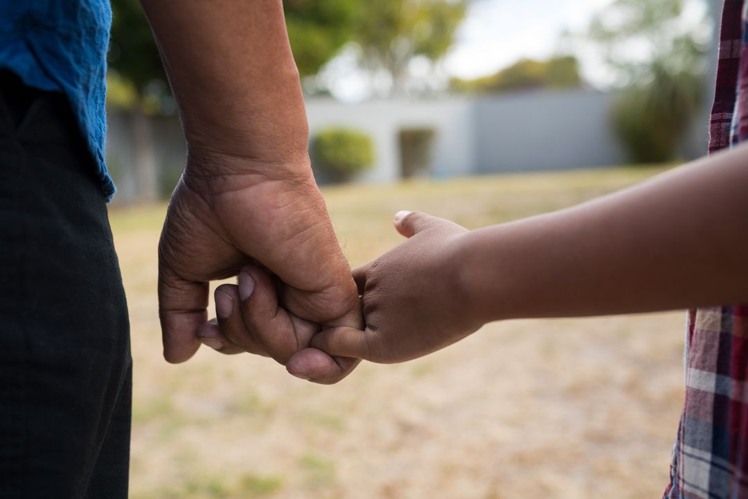 Close up of grandfather and grandson holding fingers while standing in yard Free Stock Images from PikWizard