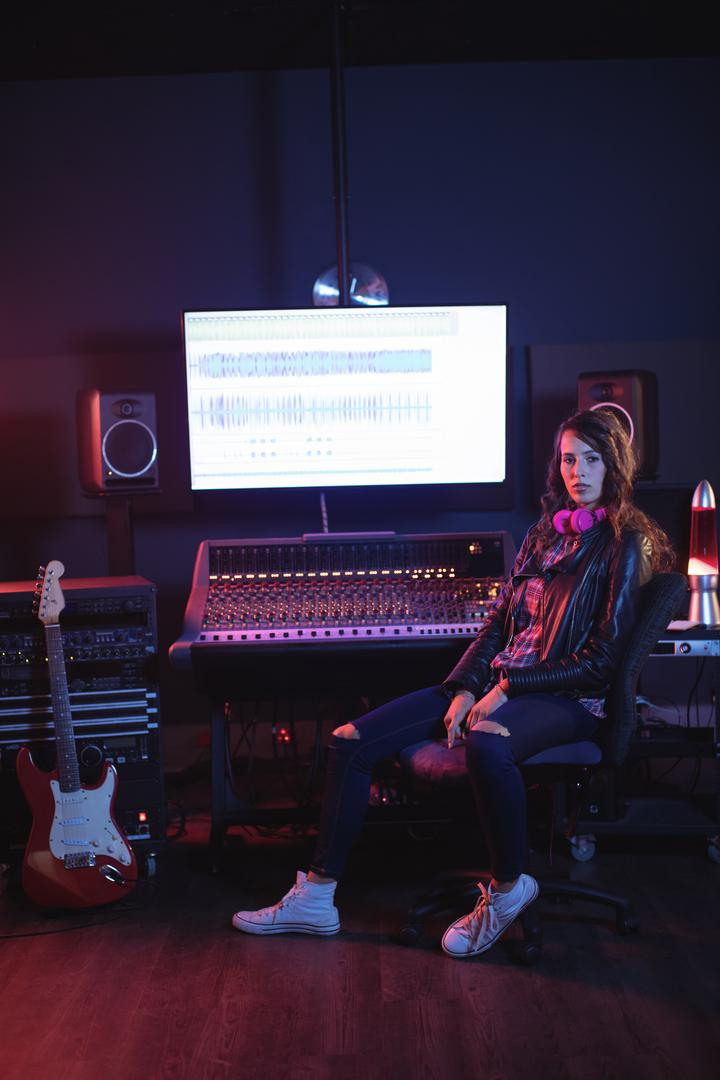 Portrait of female audio engineer sitting in recording studio