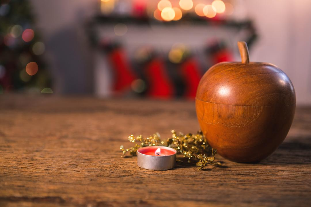 Wooden apple with tealight candle on wooden table during christmas time