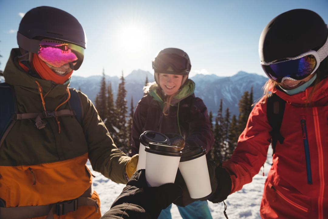 Smiling skiers toasting cup of coffees on snow covered mountain