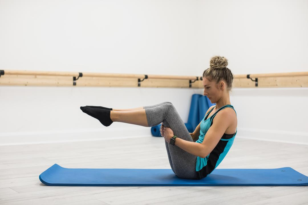 Woman performing stretching exercise in gym