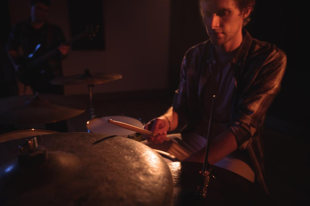 Drummer playing on drum set in recording studio