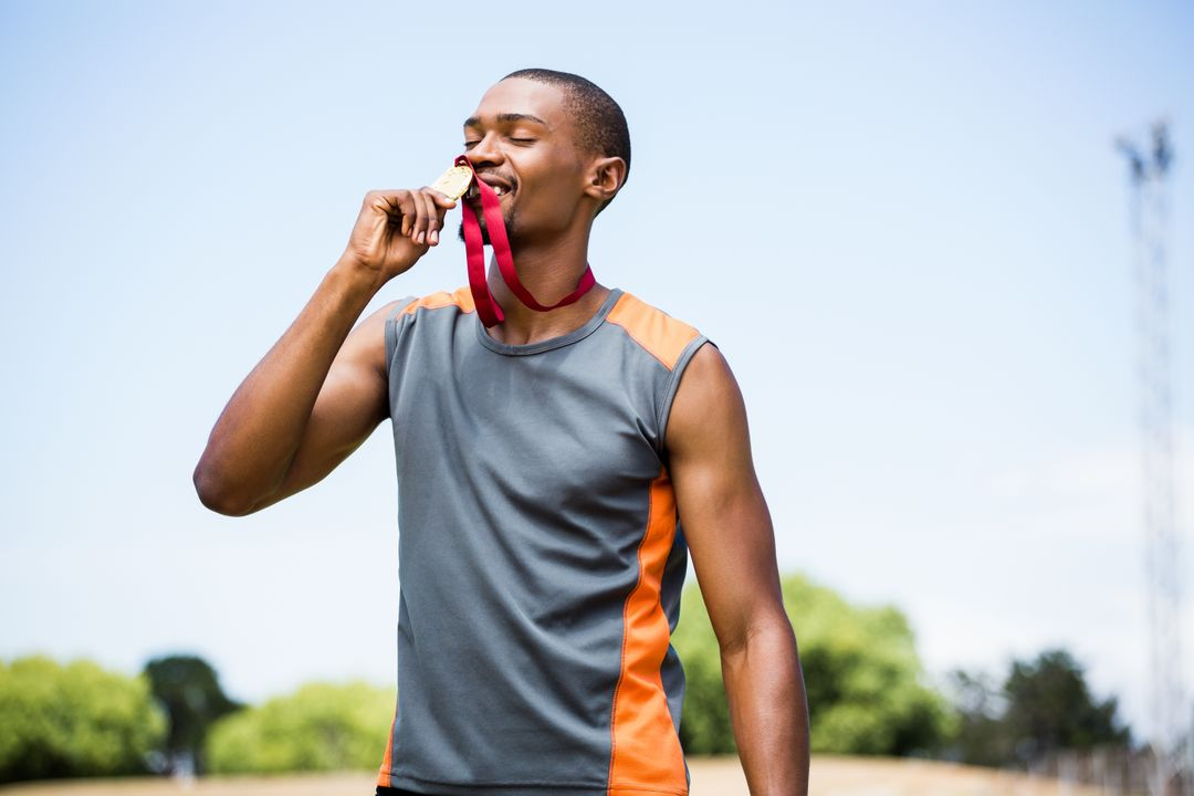 Athlete kissing his gold medal in a stadium Free Stock Images from PikWizard