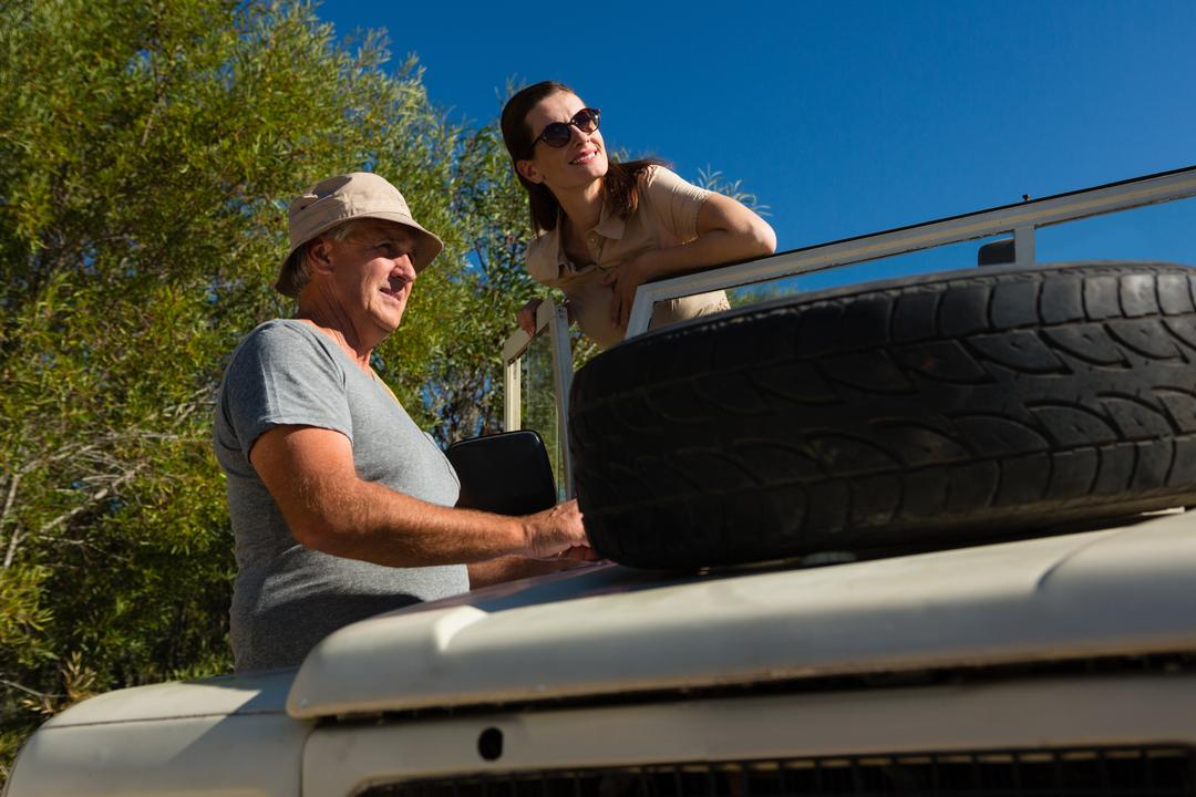 Couple looking away while standing by off road vehicle