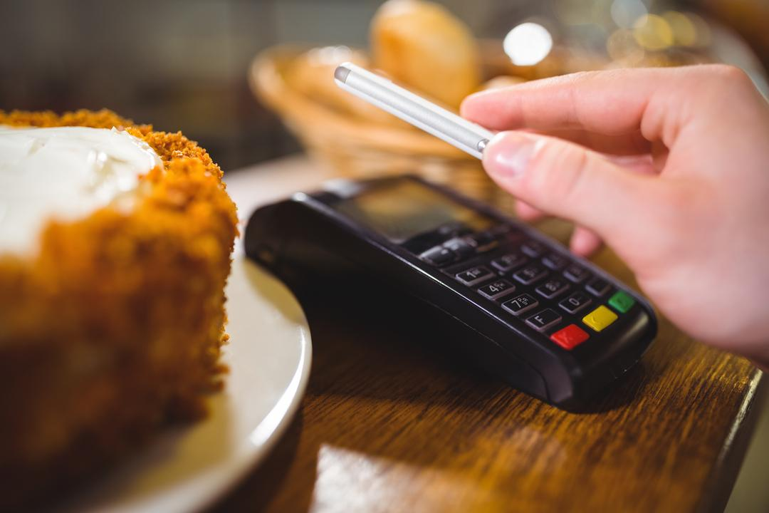Woman paying bill through smartphone using NFC technology in cafe