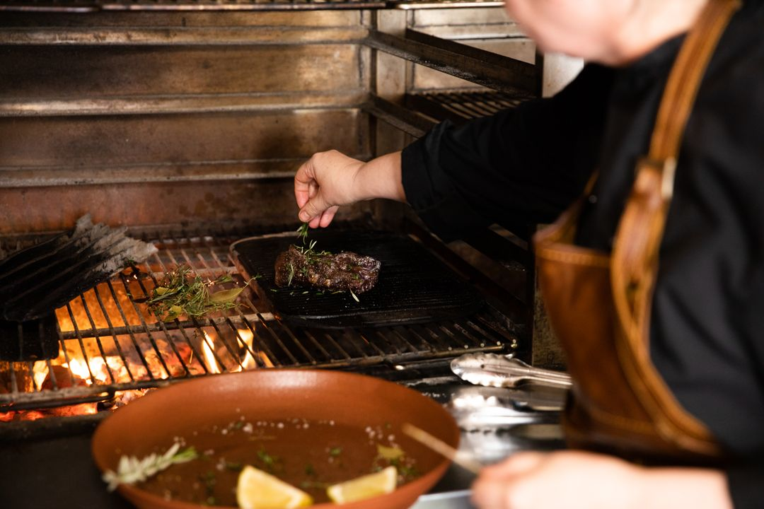 Side view close up of a Caucasian male chef working in a restaurant kitchen, putting fresh herbs on a grilled steak