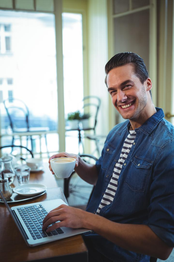 Portrait of smiling man using laptop while having coffee in café