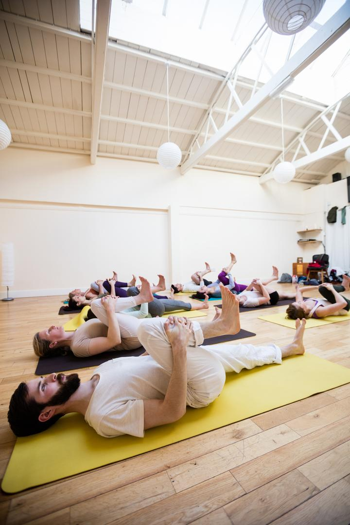 Group of people performing stretching exercise in fitness studio