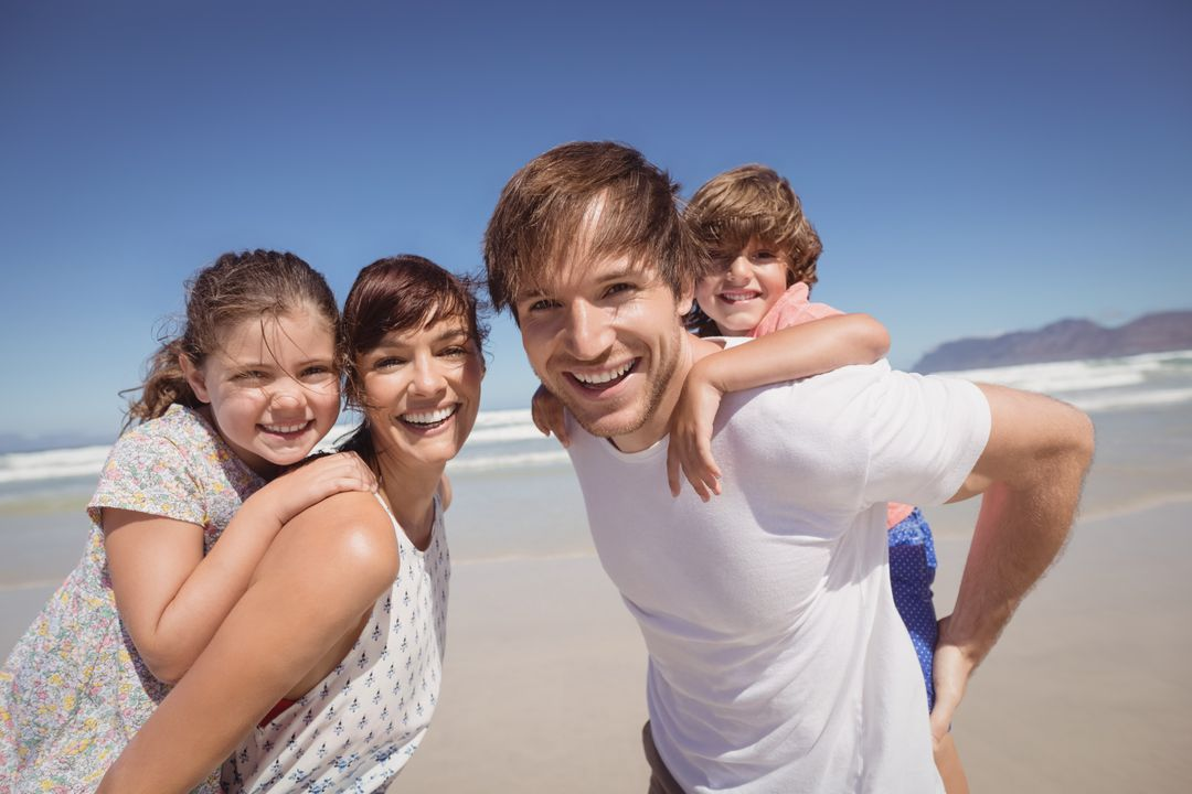 Portrait of family smiling together at beach against clear blue sky Free Stock Images from PikWizard