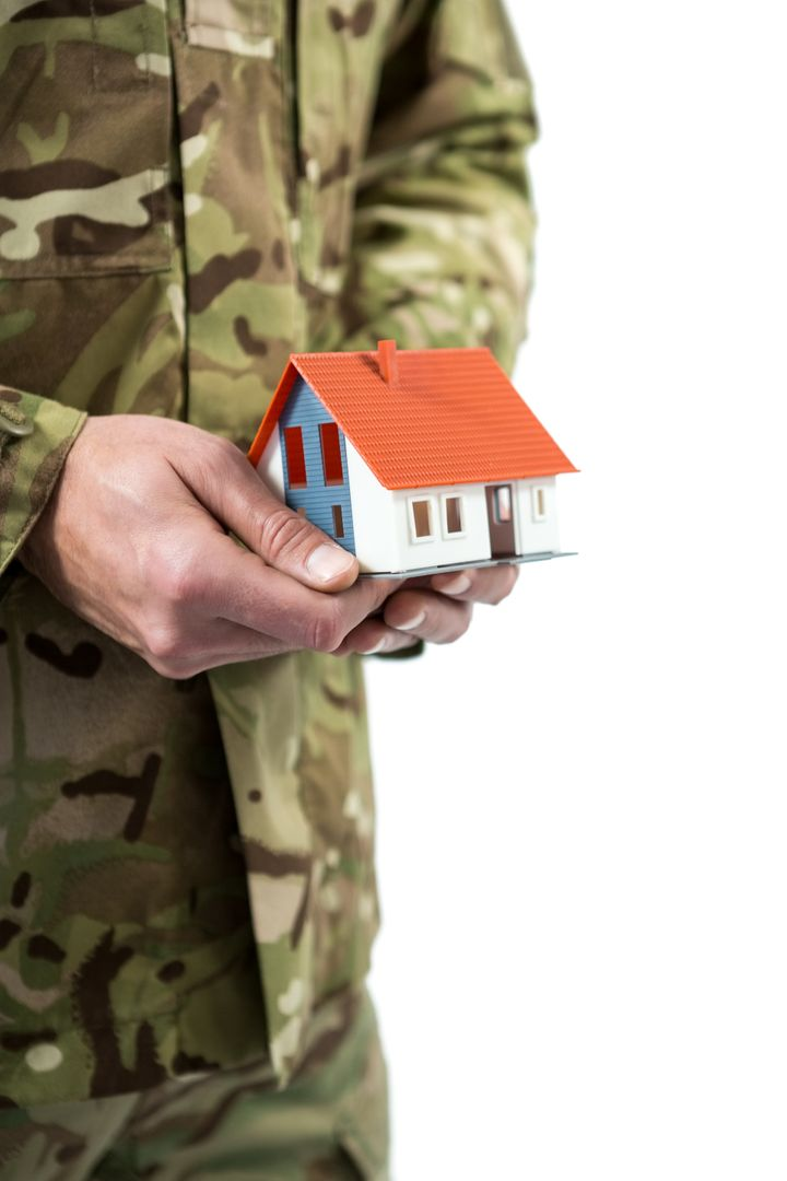 Mid section of soldier holding a model home against white background Free Stock Images from PikWizard
